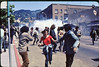 5*Thu, May 15, 1969 Subject: running from tear gas explosion*Place: Bancroft/Telegraph, Berkeley Comments: The 1st tear gas of People's Park protest (ppp). Police coming up Telegraph to campus - on right.  Observers on roof.  I was photographed here and am in the 1969 Book on PP.11 of my photos are in the 2009 book on PP.